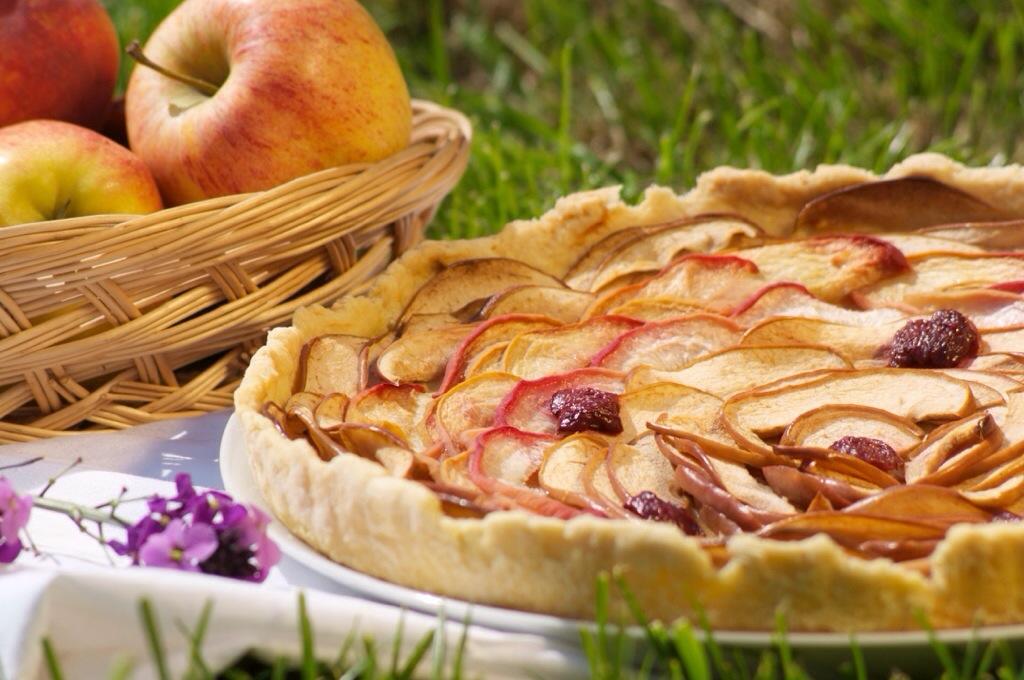 Une tarte pommes, pêches décorée de cerises